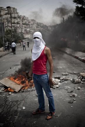 Palästinensischer Jugendlicher vor Straßenbarrikade
